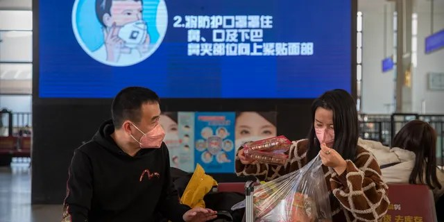 Travelers wear face masks as a screen shows a video about the proper way to wear a mask at the Beijing Railway Station in Beijing, Friday, Jan. 31. (AP Photo/Mark Schiefelbein)