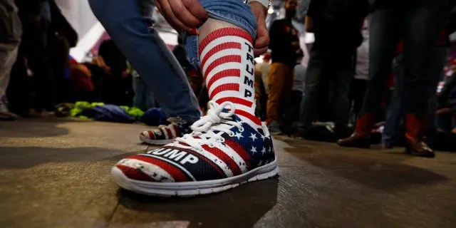 Tracy Kime of Colorado Springs, Colo., showing her shoes and socks while waiting for Trump to take the stage. (AP Photo/David Zalubowski)