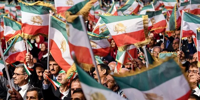 "Mujahedin-e Khalq members wave Iranian flags during the conference ""120 Years of Struggle for Freedom Iran"" at the Ashraf-3 camp, which is a base for the People's Mojahedin Organization of Iran (PMOI, MEK) in Manza, on July 13, 2019."