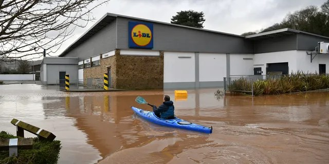 A man travels by boat through floodwater in Monmouth, Wales, Tuesday Feb. 18, 2020.