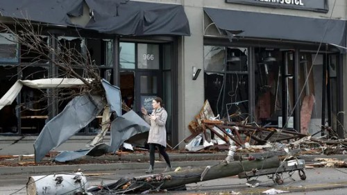 A woman walks past buildings damaged by storms Tuesday, March 3, 2020, in Nashville, Tenn.