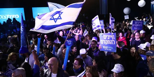 """Blue and White party supporters hold banners and flags during an election campaign rally in Tel Aviv, Israel, Saturday, Feb. 29, 2020. The Hebrew writing say """" Must to advance """". (AP Photo/Oded Balilty)"""