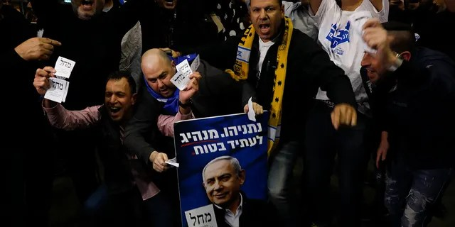 Israeli Prime Minister Benjamin Netanyahu's supporters celebrate first exit poll results for the Israeli elections at his party's headquarters in Tel Aviv, Israel, Monday, Feb. 2, 2020. (AP Photo/Ariel Schalit)
