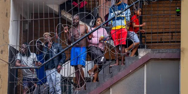Residents of the densely populated Hillbrow neighborhood of downtown Johannesburg, confined in an attempt to prevent the spread coronavirus, stand on a staircase.