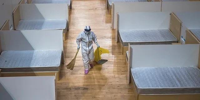 In this March 8, 2020, photo released by Xinhua News Agency, a staff member clean up an empty makeshift hospital in Wuhan, central China's Hubei Province. (Xiao Yijiu/Xinhua via AP)