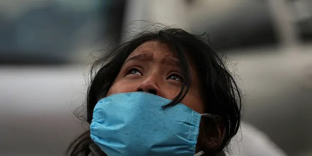 Aurora Guadalupe Azamar reacts after learning that her mother died, probably of COVID-19 disease, outside of a public hospital at Iztapalapa, Mexico City, Wednesday, April 29, 2020. At hospitals across the capital where coronavirus patients are being treated, family members of the sick crowd the sidewalk outside, with most saying they have no other way of getting information about their loved ones isolated inside. Mexico's coronavirus cases have begun rising more rapidly, with experts predicting a peak around the second week in May. (AP Photo/Fernando Llano)
