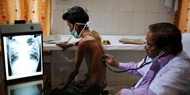 FILE - In this March 24, 2014, file photo, a doctor examines a tuberculosis patient in a government TB hospital in Allahabad, India. (AP Photo/Rajesh Kumar Singh, File)