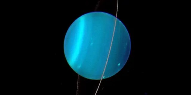 Uranus is uniquely tipped over among the planets in our Solar System. Uranus' moons and rings are also orientated this way, suggesting they formed during a cataclysmic impact which tipped it over early in its history. (Credit: Lawrence Sromovsky, University of Wisconsin-Madison/W.W. Keck Observatory/NASA)