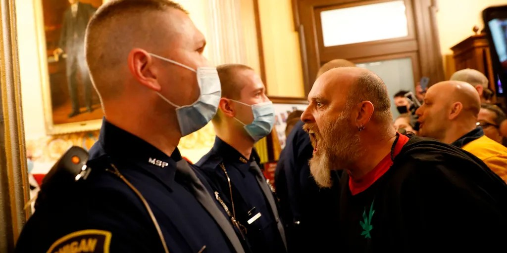 Michigan man in infamous photo shouting in police's face unmasked ...