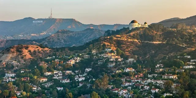 Aerial view of the Griffith Observatory on Mount Hollywood and the Hollywood Sign seen in the distance, California, USA.