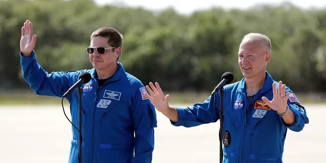 NASA astronauts Bob Behnken, left, and Doug Hurley wave as they leave a news conference after they arrived at the Kennedy Space Center in Cape Canaveral, Fla., Wednesday, May 20, 2020.