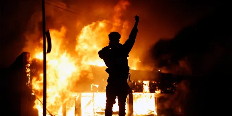 A check-cashing business burns during protests in Minneapolis on May 29, 2020. Protests continued following the death of George Floyd, who died in police custody in Minneapolis on Memorial Day. (AP Photo/John Minchillo)