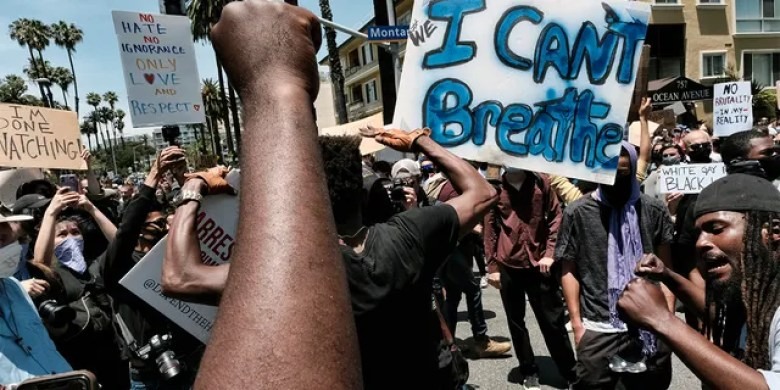 Protesters chant and raise their fists while blocking traffic on a street corner in Santa Monica, Calif., Sunday, May 31, 2020, over the death of George Floyd, a black man who died May 25 after he was pinned at the neck by a Minneapolis police officer.