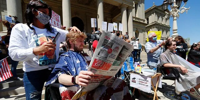 Jody Hebberd, left, gives a free haircut to Reid Scott, as he reads the paper on the steps of the State Capitol as Karl Manke, right, cuts the hair of Parker Shonts during a rally in Lansing, Mich., on Wednesday. (AP Photo/Paul Sancya)