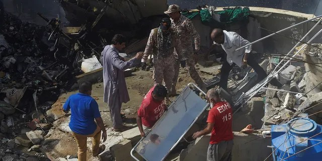 Rescue workers gather at the site after a Pakistan International Airlines flight crashed in a residential neighbourhood in Karachi on May 22, 2020.