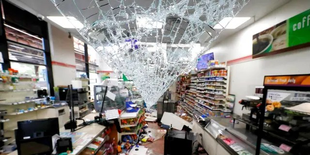 Shattered glass hangs from the doorway of a 7-Eleven store May 31, 2020, in Chicago. (AP Photo/Charles Rex Arbogast)