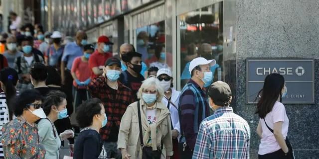Люди носят защитные маски возле банка в районе Квинс, Нью-Йорк, 8 июня 2020 года. (Ассошиэйтед Пресс)