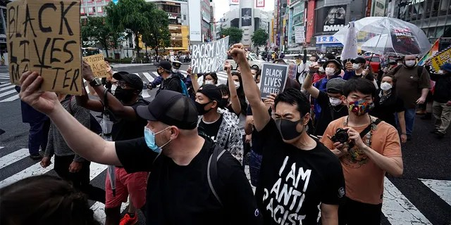 People march to protest during a solidarity rally for the death of George Floyd in Tokyo Sunday, June 14, 2020. Floyd died after being restrained by Minneapolis police officers on May 25.