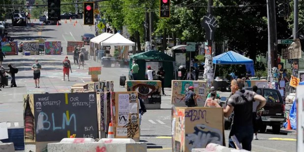 People walk through the barricades in what has been called the Capitol Hill occupied protest area in Seattle on Monday, June 22, 2020. For the second time in less than 48 hours, there was a shooting near the