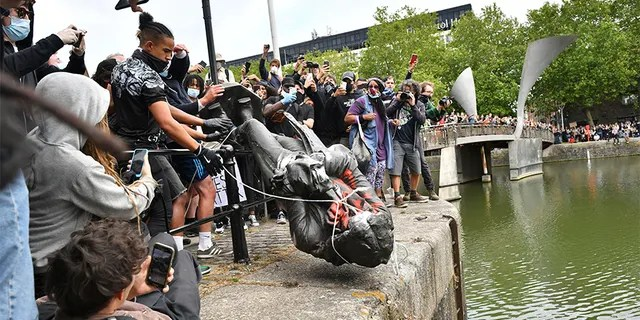 Протестующие бросают статую работорговца Эдварда Колстона в бристольскую гавань во время акции протеста Black Lives Matter в Бристоле, Англия, в воскресенье. (AP / PA)