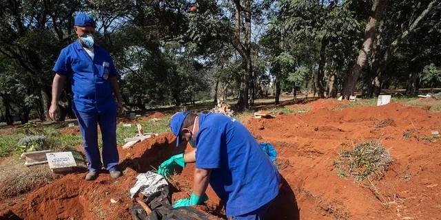Работники кладбища эксгумируют тело, которое было похоронено три года назад на кладбище Вила-Формоза, которое не взимает плату с семей за могилы в Сан-Паулу, Бразилия, в пятницу, 12 июня 2020 года. Через три года после захоронений останки обычно эксгумируются и хранятся в полиэтиленовых пакетах, чтобы освободить место для новых захоронений, которые увеличились на фоне нового коронавируса. (AP Photo / Андре Пеннер)