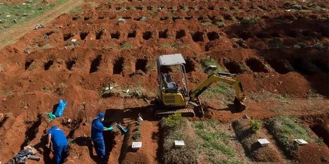 Работники кладбища эксгумируют останки, похороненные три года назад на кладбище Вила-Формоза, которое не взимает плату с семей за захоронения, в Сан-Паулу, Бразилия, в пятницу, 12 июня 2020 года. Через три года после захоронений останки обычно эксгумируются и хранятся в полиэтиленовых пакетах. чтобы освободить место для новых захоронений, которые увеличились на фоне нового коронавируса. (AP Photo / Андре Пеннер)