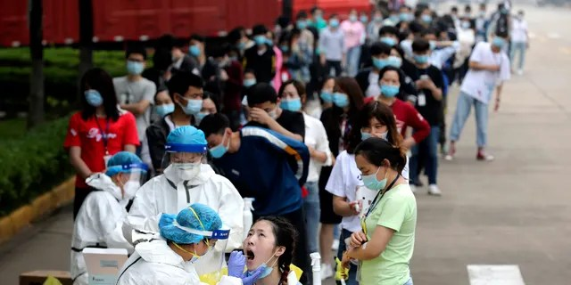 People line up for medical workers to take swabs for the coronavirus test at a large factory in Wuhan in central China's Hubei province on May 15.