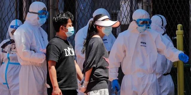 Работники в защитных костюмах направляют людей, которые либо проживают на оптовом рынке Xinfadi, либо посещают рынок, чтобы пройти тест на нуклеиновые кислоты на стадионе в Пекине, воскресенье, 14 июня 2020 года.