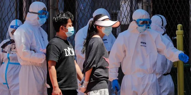 Workers in protective suits direct people who were either living surrounding the Xinfadi wholesale market or have visited the market to get a nucleic acid test at a stadium in Beijing, Sunday, June 14, 2020.