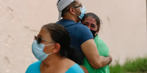 People hug each other on the street as they wait for everything cleared to return to their apartment after an earthquake in Mexico City, Tuesday, June 23, 2020.
