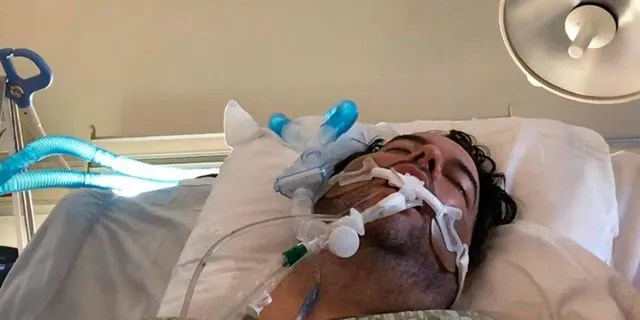 In this June 2020 photo made available by Michelle Zymet, her husband John Place breathes through a ventilator while fighting COVID-19 in an ICU bed at Westside Regional Medical Center in Plantation, Fla. (Michelle Zymet)