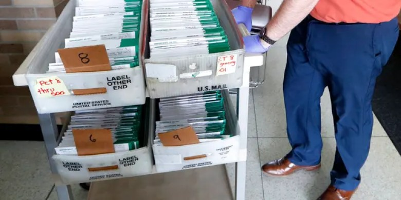 In this May 5, 2020, file photo, Jordan Smellie moves absentee ballots to be counted at City Hall in Garden City, Mich. (AP Photo/Paul Sancya, File)