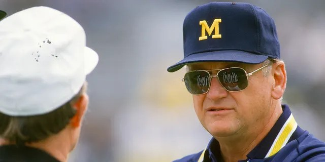 Head Coach Bo Schembechler of the Michigan Wolverines talks with an official while his team warms up before the start of an NCAA football game circa 1986.