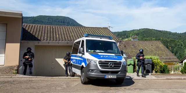 Police remain by a police car in Oppenau, Germany, Monday July 13, 2020. German authorities say they have deployed hundreds of police in search of a 31-year-old man who disarmed four police officers under the threat of a gun Sunday, July 12, 2020. (Philipp von Ditfurth / dpa via AP)