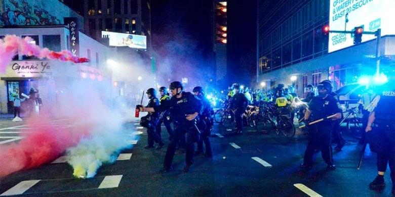 Smoke rises around police as they use pepper spray during clashes with protesters after a May 31 demonstration over the death of George Floyd. (Photo by JOSEPH PREZIOSO/AFP via Getty Images)