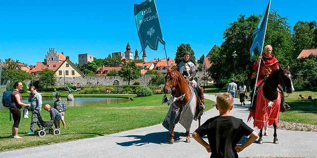 Thomas Lindgren (left) on the Soprano horse and Anders Mansson on Sara, both of the Tornamenteum knight society, patrol the town of Visby on the Swedish island of Gotland on July 23, 2020 (SOREN ANDERSSON / TT News Agency / AFP via Getty Images)