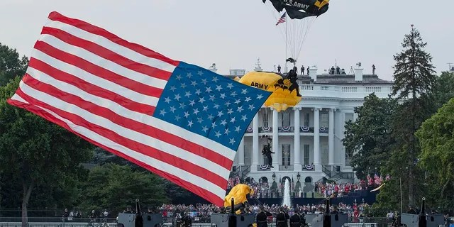 """President Donald Trump and first lady Melania Trump watch as the U.S. Army Golden Knights Parachute Team descend during a """"Salute to America"""" event on the South Lawn of the White House, Saturday, July 4, 2020, in Washington. (AP Photo/Alex Brandon)"""