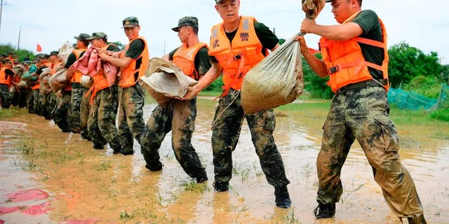 In this photo published by the Xinhua News Agency, Chinese paramilitary police line up to move sandbags to strengthen a seawall along the shores of Poyang Lake in Poyang County, Jiangxi Province, in is from China on July 12.