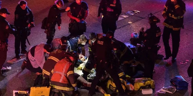 Emergency workers tend to an injured person on the ground after a driver sped through a protest-related closure on the Interstate 5 freeway in Seattle early Saturday. (James Anderson via AP)