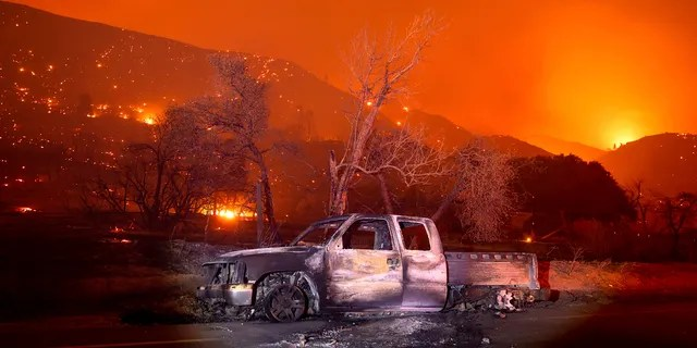 A scorched vehicle rests on Pine Canyon Rd. as the Lake Fire burns a hillside in the Angeles National Forest, Calif., north of Santa Clarita on Thursday, Aug. 13, 2020.