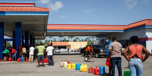 Residents line up to fill their containers with gasoline before Hurricane Isaias arrives in Freeport, Grand Bahama, Bahamas on Friday, July 31, 2020 (AP Photo / Tim Aylen)