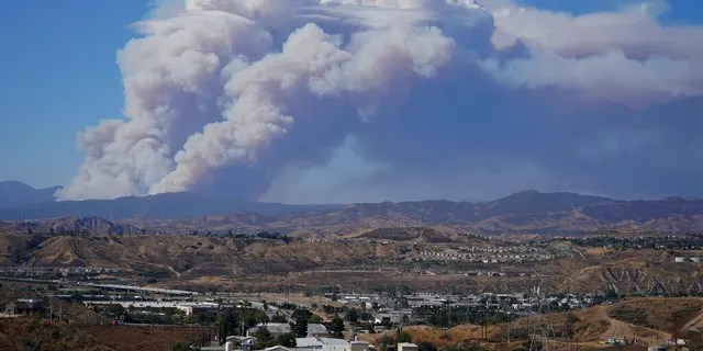 The Lake Fire sends a plume of smoke over the Angeles National Forest Wednesday, Aug. 12, 2020, in a view from Santa Clarita, Calif. (AP Photo/Marcio Jose Sanchez)