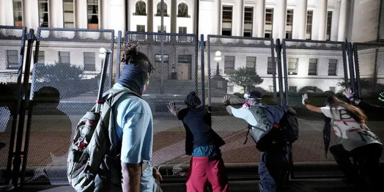 People trying to push over protective fencing Tuesday in Kenosha. (AP Photo/Morry Gash)