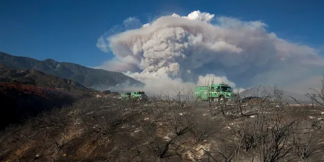 Some rises behind an area burned by a brush fire at the Apple Fire in Cherry Valley, Calif., Saturday, Aug. 1, 2020.
