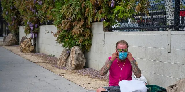 A homeless man in West Hollywood puts on his face mask during the COVID-19 outbreak. (iStock)