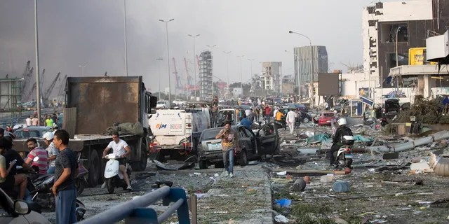 People evacuate wounded after of a massive explosion in Beirut, Lebanon, Tuesday, Aug. 4, 2020. Massive explosions rocked downtown Beirut on Tuesday, flattening much of the port, damaging buildings and blowing out windows and doors as a giant mushroom cloud rose above the capital. Witnesses saw many people injured by flying glass and debris.