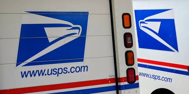 FILE: Mail delivery vehicles are parked outside a post office in Boys Town, Neb.