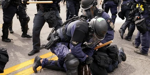 Police detain a protester, Wednesday, Sept. 23, 2020, in Louisville, Ky. (Associated Press)