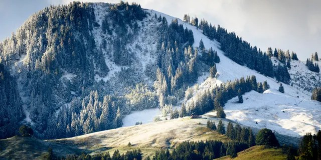 Fresh snow is visible on the slopes of Moleson Mountain near the still green pastures on Saturday, September 26, 2020, in Moleson en Gruyère, Switzerland.