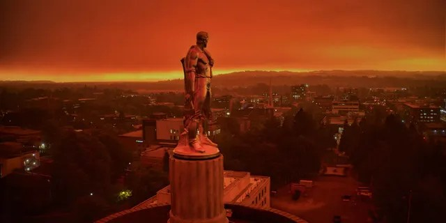 """This drone photo provided by Michael Mann shows the Oregon Capitol building, with its """"Oregon Pioneer"""" bronze sculpture atop the dome, with skies filled with smoke and ash from wildfires as a backdrop in Salem, Ore., on Sept. 8, 2020."""